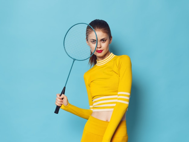 A woman with a stylish tracksuit does sports and does exercises, a yellow tracksuit,