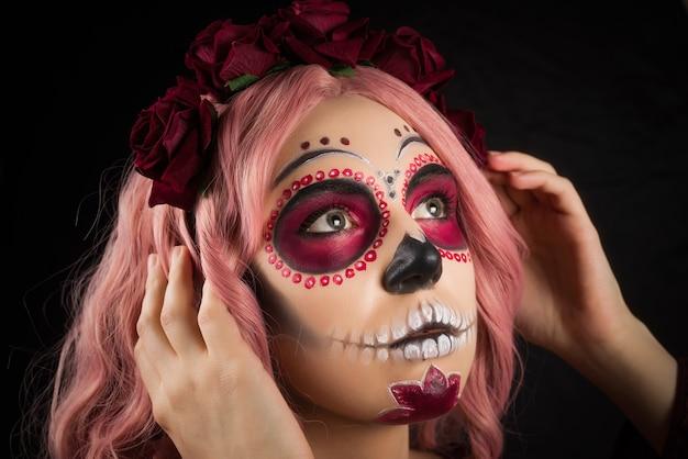 黒の背景に分離された砂糖の頭蓋骨メイクとピンクの髪を持つ女性