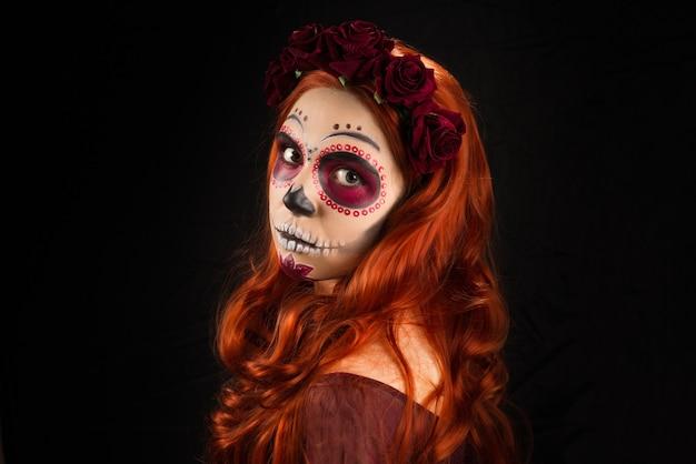 Женщина с макияжем сахарного черепа и рыжими волосами, изолированными на черном фоне