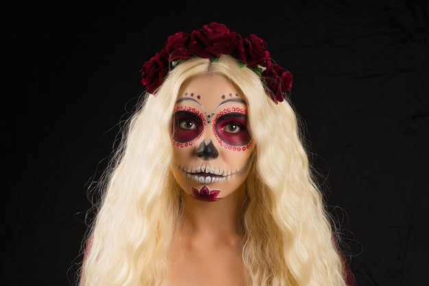 Woman with sugar skull makeup and blond hair isolated on black background. day of the dead. halloween.  copy space.