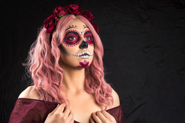 Woman with sugar skull makeup and pink hair isolated on black background. day of the dead. halloween.  copy space.