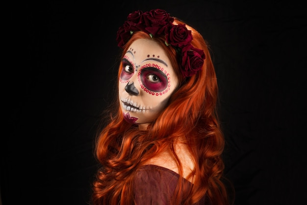 Woman with sugar skull makeup and red hair isolated on black background