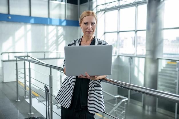 Женщина с чемоданом и открытым ноутбуком, стоя в аэропорту