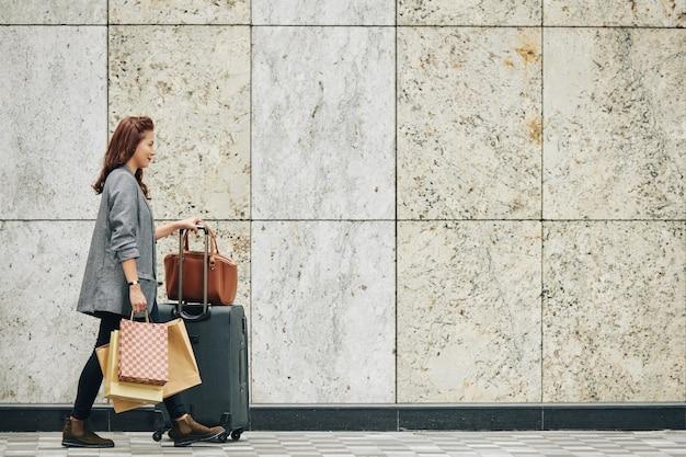 スーツケースと買い物袋を持つ女性