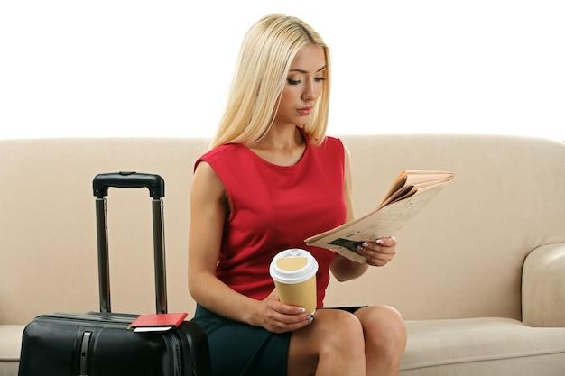 ソファに座って、白で隔離の新聞を読んでスーツケースとタブレットを持つ女性