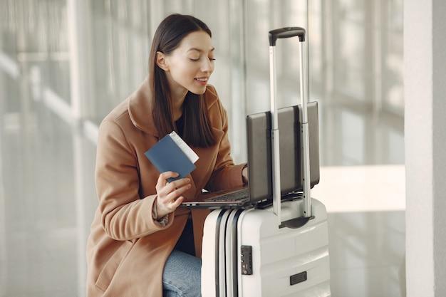 空港でスーツケースを持つ女性