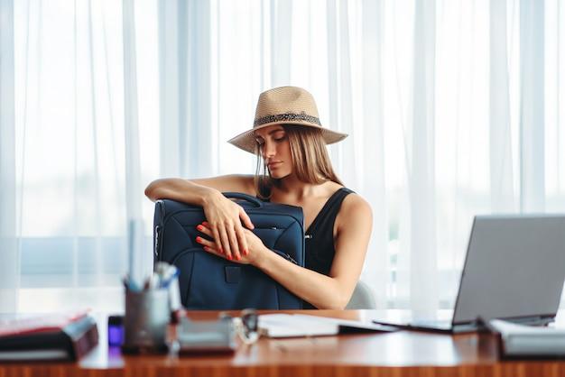 Женщина с чемоданом за столом в офисе мечтает о путешествии.