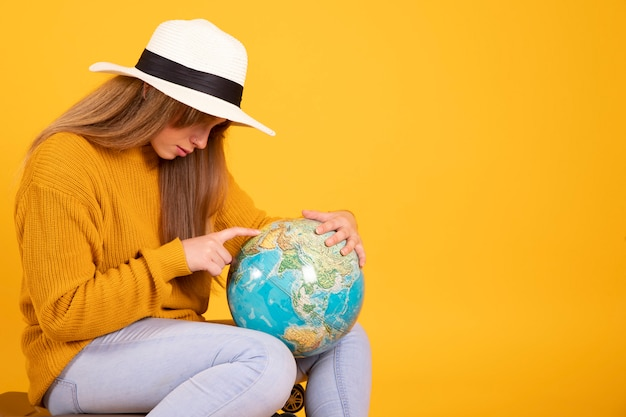 Woman with suitcase and hat looks at earth globe wants to travel