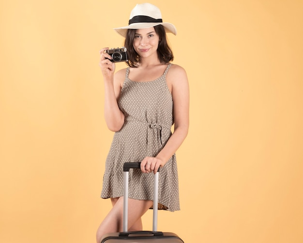 Woman with suitcase hat and photo camera traveler, tourist. on yellow background
