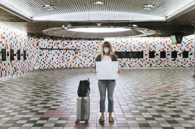 Woman with a suitcase holding a blank paper during the coronavirus outbreak