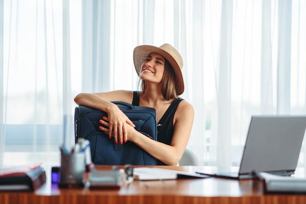Женщина с чемоданом в офисе мечтает о путешествии