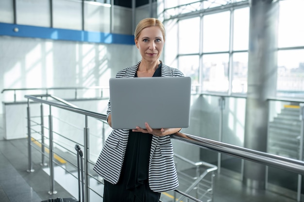 Woman with suitcase and open laptop standing at airport