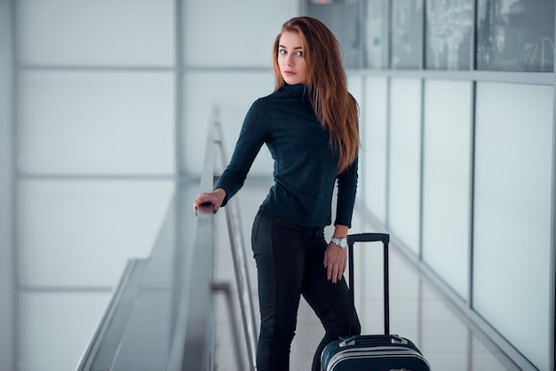 ガラス張りのバルコニーでポーズのスーツケースを持つ女性。