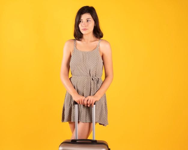 休暇に行く準備ができているスーツケースを持つ女性