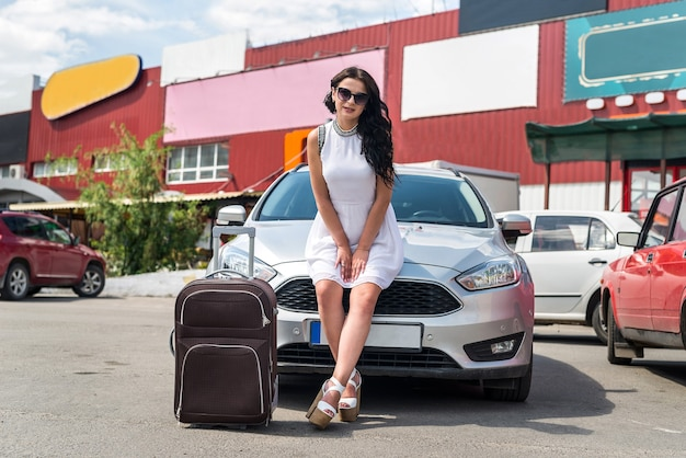車のボンネットに座っているスーツケースを持つ女性