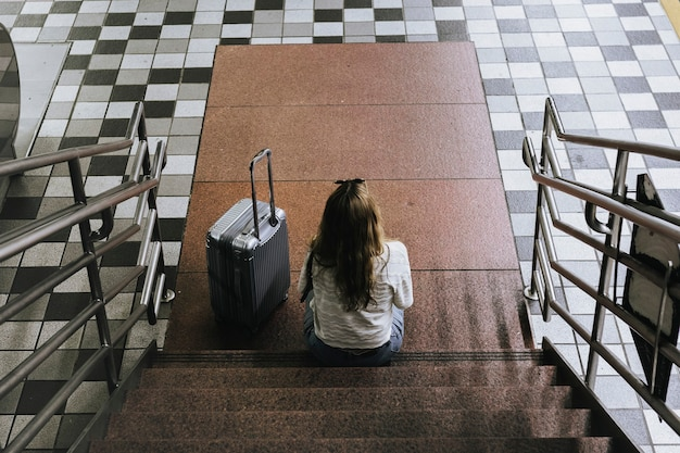 Woman with a suitcase sitting on the stairs waiting for the train during the coronavirus outbreak