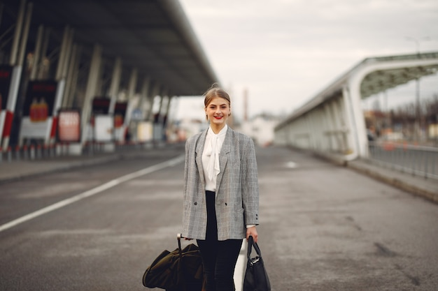 Woman with suitcase standing by the airport