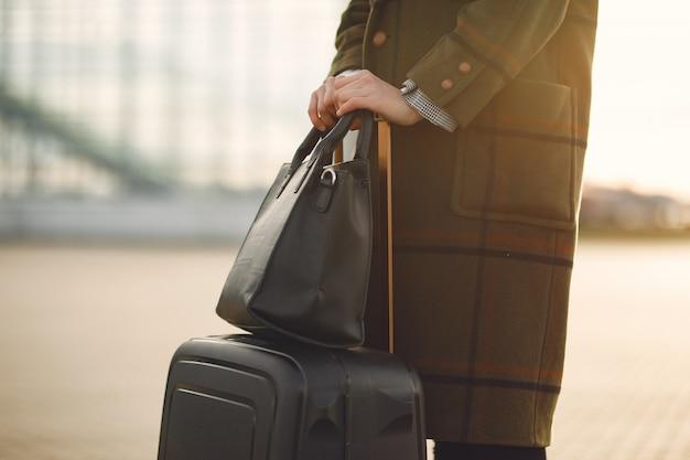 Женщина с чемоданом стоял у аэропорта