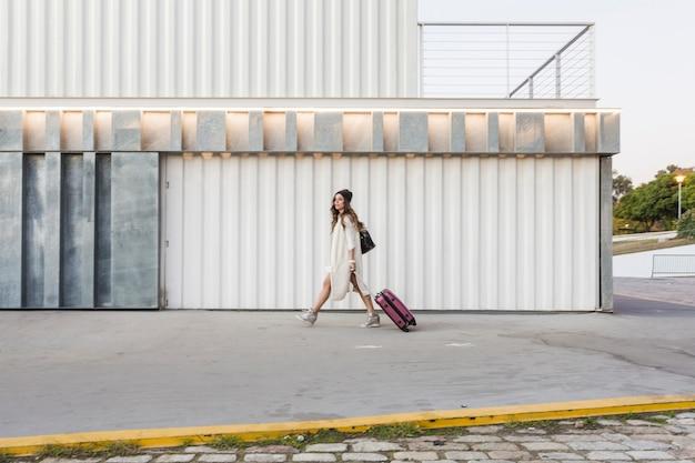 Женщина с чемоданом, идущим по улице