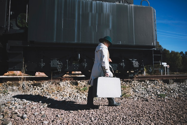 Woman with suitcase walking to train
