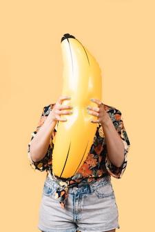 彼女の顔の前に膨脹可能なバナナを保持している夏服の女性