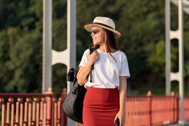 Женщина в солнцезащитных очках и шляпе путешествует одна