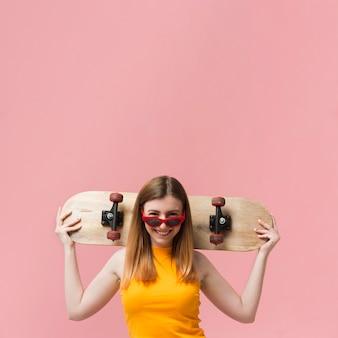 Женщина в солнцезащитных очках и скейтборде с копией пространства