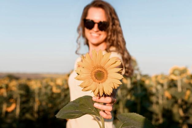 Женщина в солнцезащитных очках с подсолнухом