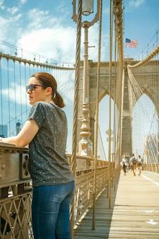 뉴욕 맨해튼 스카이라인을 배경으로 브루클린 다리에서 도시 경관을 바라보는 선글라스를 쓴 여성