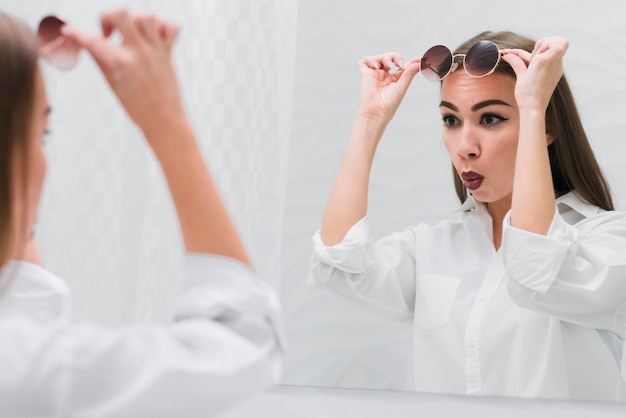 Woman with sunglasses looking in the mirror