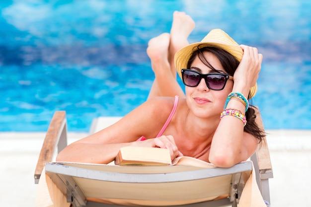 La donna con gli occhiali da sole in posa con un libro