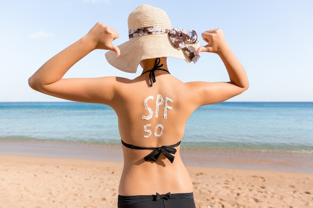 Woman with sunscreen in form of spf 50 word on her back sunbathing at the beach
