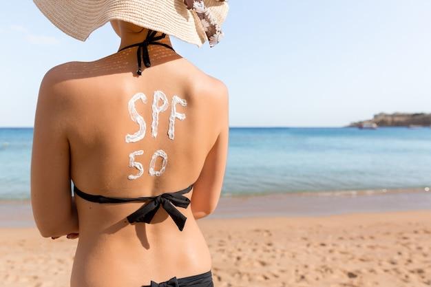 Spf 50 단어의 형태로 자외선 차단제를 착용 한 여성이 해변에서 일광욕을하고 있습니다. 태양 보호 계수 개념.