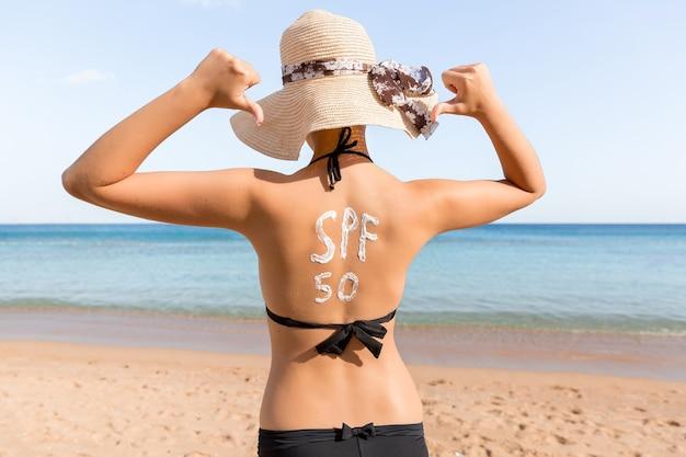 ビーチで日光浴をしている彼女の背中にspf50ワードの形で日焼け止めを持っている女性