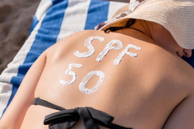 Spf 50 단어 형태의 자외선 차단제를 착용 한 여성이 해변에서 일광욕 용 침대에서 일광욕을하고 있습니다. 태양 보호 계수 개념.