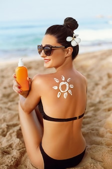 Woman with suntan lotion on beach in form of the sun