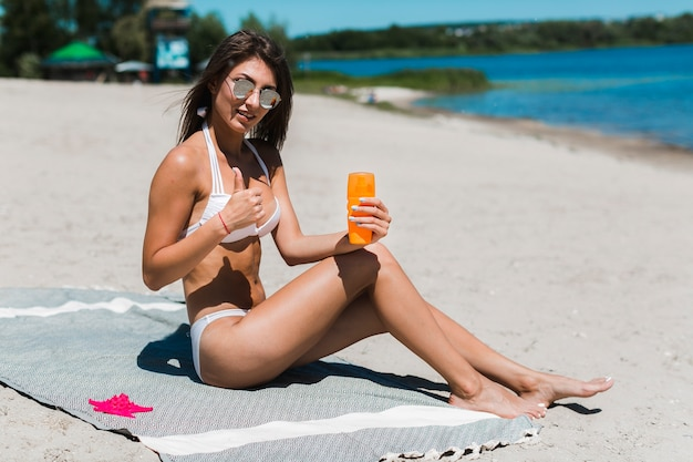 Woman with suntan lotion gesturing thumb-up
