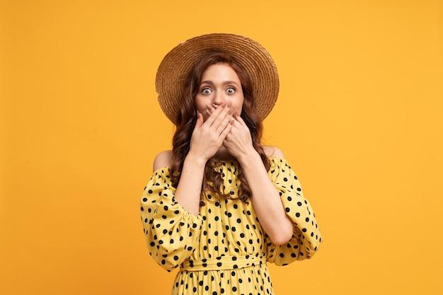 Suprice 얼굴을 가진 여자는 그녀의 손으로 그녀의 입을 죄수합니다. 밀짚 모자를 쓰고 세련된 여름 드레스를 입고 있습니다.