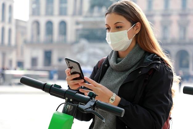 サージカルマスクを持った女性が携帯電話で電動スクーターのロックを解除する