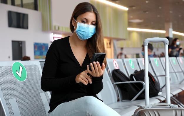 空港で待っているサージカルマスクを持つ女性