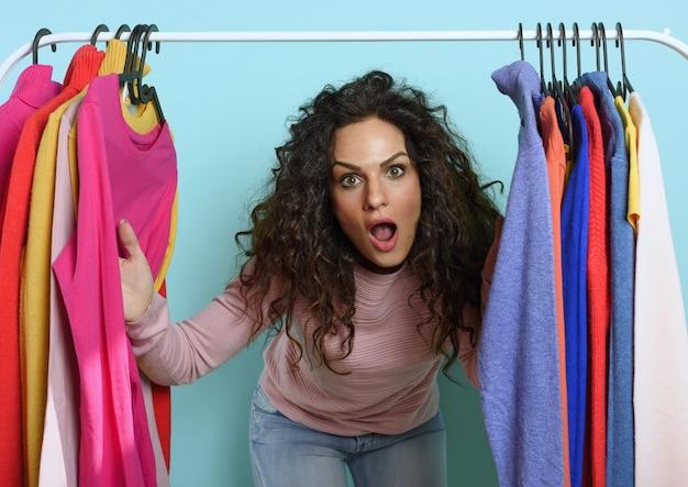 驚きの表情の女性がお店で買う服を選びます。ショッピングと買い物中毒の概念。