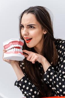 びっくりした顔と口を開けた女性。開いた教育歯科医の顎を顔の近くに持っている少女。歯科の概念。面白い感情。
