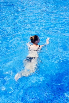 Woman with swimsuit swimming on a blue water pool, tropical vacation holiday concept