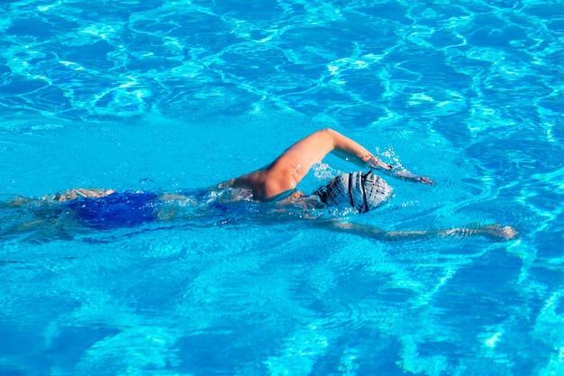 Женщина с купальником плавает в бассейне с голубой водой. спорт.