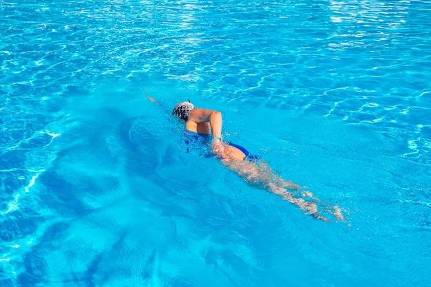 Женщина с купальником плавает в бассейне с голубой водой.