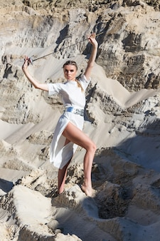 砂漠で合計白い衣装で剣を持つ女性