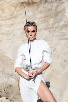 Woman with sword in total white outfit in desert