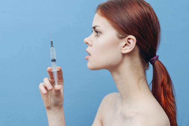 Женщина со шприцем в руках на синем фоне, вид сбоку инъекции ботокса омоложения