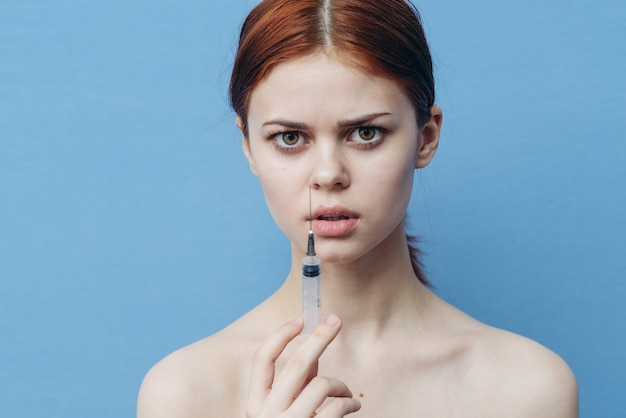 Женщина со шприцами в руке делает инъекцию ботокса для омоложения лица