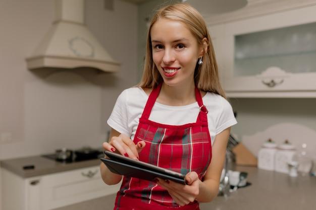 キッチンでタブレットを持つ女性